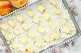 Melocotones cubiertos con mezcla de pastel y mantequilla para hacer un pastel de volcado de durazno.