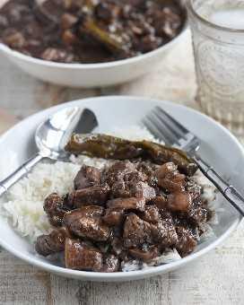 dinuguan sobre arroz al vapor en un plato blanco