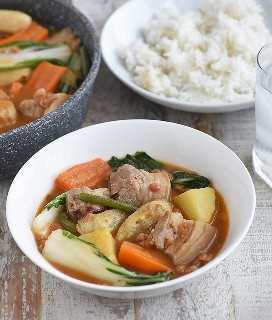pocherong baboy con carne de cerdo y frijoles, plátano, papas, zanahorias y pechay en un tazón blanco con un plato de arroz al vapor al lado