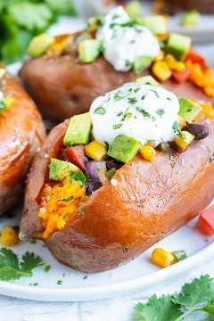 Taco relleno de batatas con frijoles negros y maíz para una receta de cena vegana.