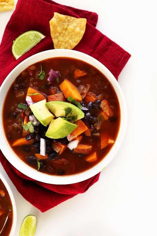 Tazón de nuestra receta vegana de chile con frijoles negros y camote cubierto con aguacate