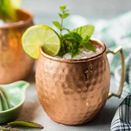 Una bebida mula helada de Moscú en una taza de cobre, adornada con limón y menta fresca.