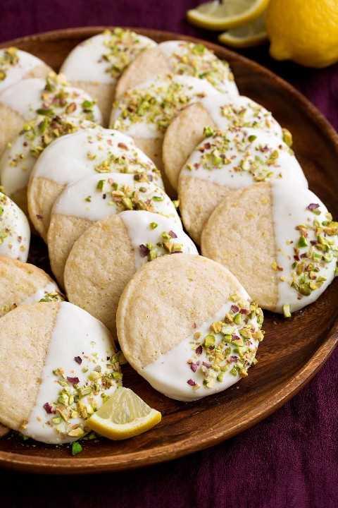 Galletas de mantequilla con sabor a limón, bañadas en chocolate blanco y espolvoreadas con pistachos. Aquí se muestra en un plato de madera.