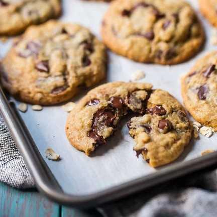 Cerrar imagen de una galleta de chispas de chocolate de avena recién horneada, partida por la mitad para revelar la fusión de chocolate negro