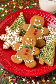 Galletas de jengibre en un plato rojo cortado en forma de hombres de pan de jengibre, árboles y copos de nieve. Decorado con glaseado real y chispas navideñas.