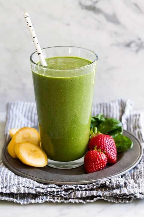 Batido verde en un vaso alto con fresas, espinacas y plátanos a un lado.