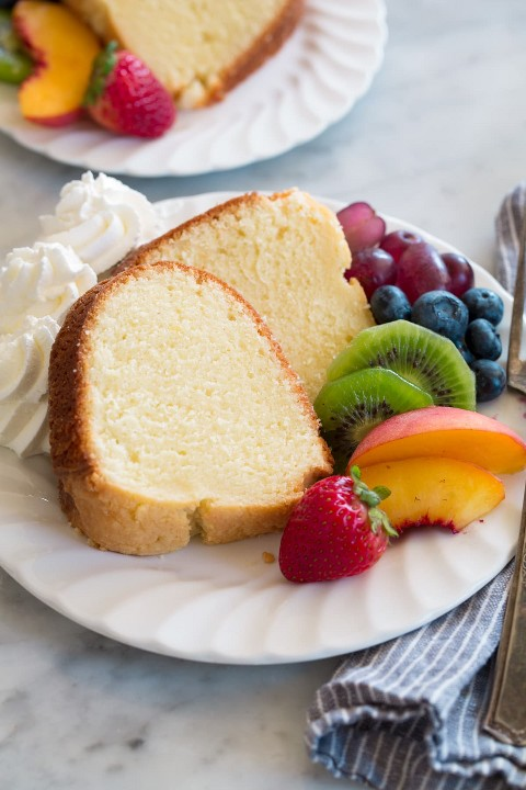 Rebanada de bizcocho en un plato de postre con un lado de fruta fresca y crema batida.