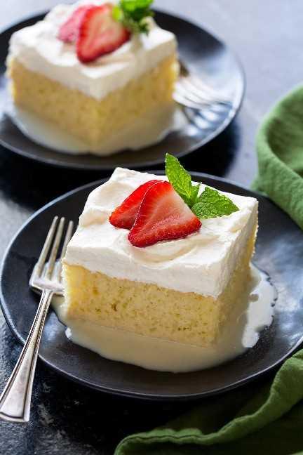 Rebanada de pastel Tres Leches en un pequeño plato de postre negro. El pastel es de color amarillo cremoso con un glaseado de crema batida blanca. Está adornado con rodajas de fresas frescas y menta en la parte superior.