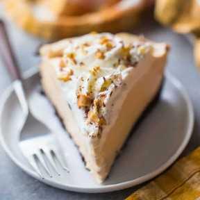 Una rebanada perfecta de pastel de mantequilla de maní con crema batida y una costra de galletas Oreo.