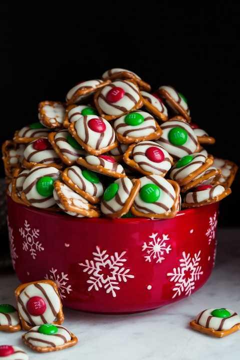 Pretzel M&M Abrazos en un cuenco rojo de copo de nieve. Consisten en una base cuadrada de pretzel, chocolate de abrazo y M & M's rojos y verdes.