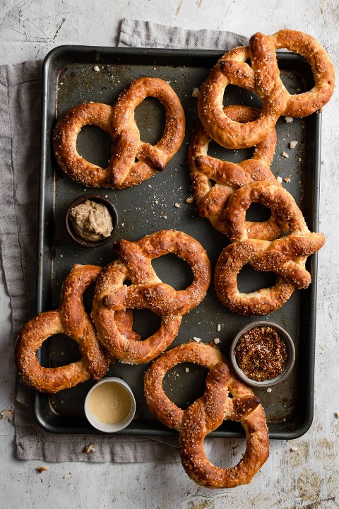 Imagen de arriba de siete pretzels suaves en una bandeja para hornear oscura.