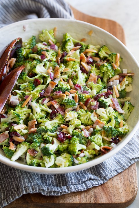 Salada de brócolis clássica em uma tigela de salada em uma placa de pão de madeira.