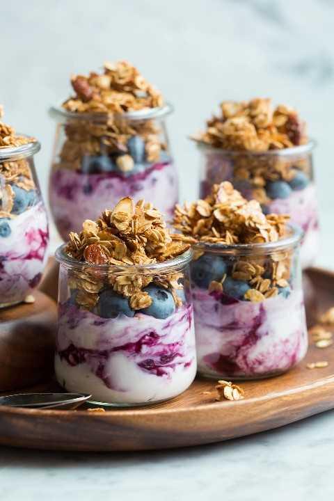 Granola casera servida en pequeños vasos de vidrio con yogur y arándanos.
