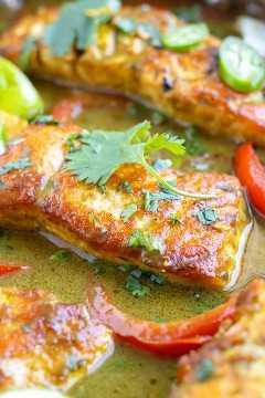 Un primer plano de un filete de salmón en una salsa de curry verde de leche de coco hecha con jugo de limón y curry en polvo.
