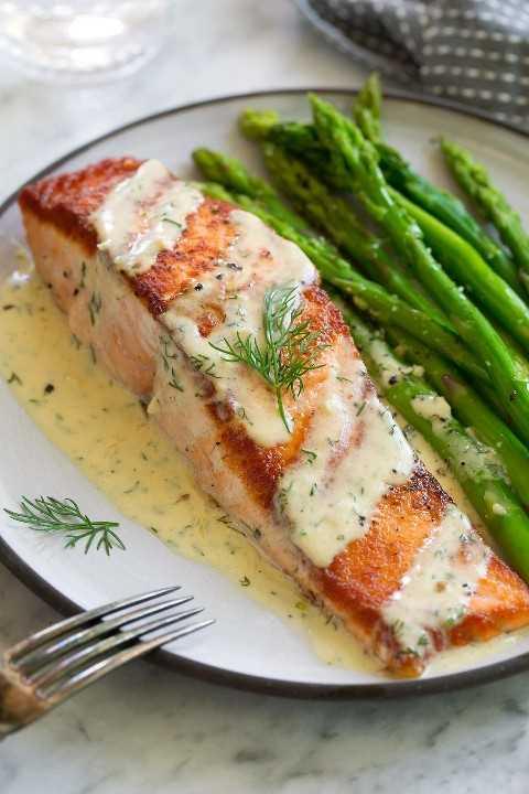 Una sola sartén chamuscado filete de salmón en un plato blanco. El salmón se rocía con una cremosa salsa de mostaza y se espolvorea con eneldo. Se sirve con un lado de espárragos.