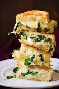Pila de cuatro mitades de sandwich de queso a la parrilla en un plato blanco. El relleno incluye queso, espinacas y alcachofas.