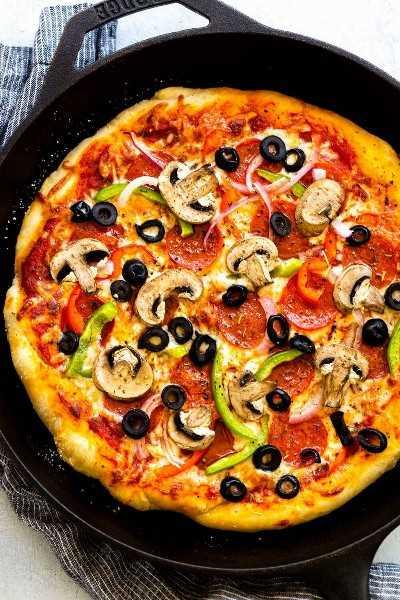 pizza suprema dentro de una sartén de hierro fundido
