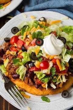 Un pan frito casero está cubierto con relleno de taco Navajo que incluye carne molida sazonada, frijoles, tomates, lechuga, aceitunas, queso y crema agria. Se coloca en un plato blanco para servir sobre una superficie de madera marrón.