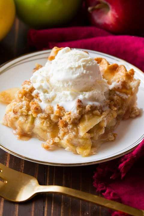 Rebanada de pastel de manzana con trozos de miga en un plato de postre blanco sobre una superficie de madera marrón. La rebanada de pastel está cubierta con helado de vainilla.