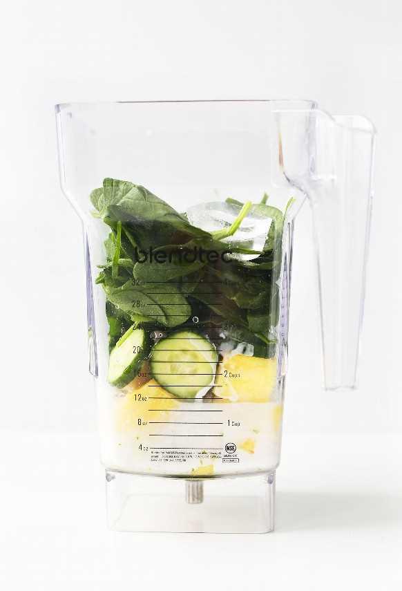 Licuadora con ingredientes para hacer un licuado verde cremoso saludable de pepino con piña