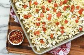 Ciérrese para arriba de las palomitas de maíz de la pizza de salchichones listas para ser cocido en una fuente de horno.