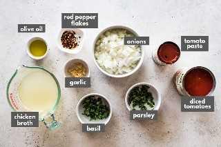 Ingredientes de salsa de arrabiata en una mesa, incluidos tomates en cubos enlatados y hojuelas de pimiento rojo.