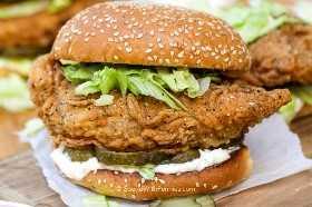 Crujiente sándwich de pollo con pepinillos, lechuga y mayonesa cubierto con un bollo de semillas de sésamo