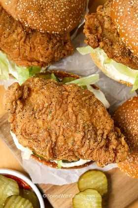 3 sándwiches crujientes de pollo en bollos de semillas de sésamo con pepinillos y lechuga
