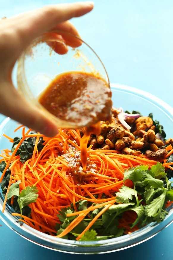 Verter el aderezo sobre nuestra ensalada de zanahoria tailandesa fácil con anacardos al curry