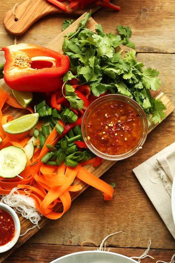Tabla de cortar de madera con ingredientes para hacer tazones de fideos tailandeses para una receta vegana fresca