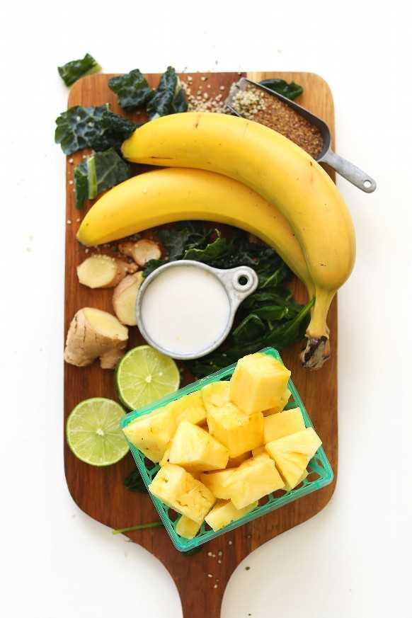 Tablero de madera con piña, plátano, leche de nuez, lima, jengibre, col rizada, semillas de cáñamo y harina de linaza
