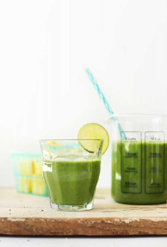Sirviendo vaso lleno de batido verde de jengibre colada con una rodaja de limón en el borde