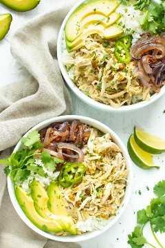 Receita lenta da tigela de Burrito de frango desintegrado do fogão em duas tigelas brancas.