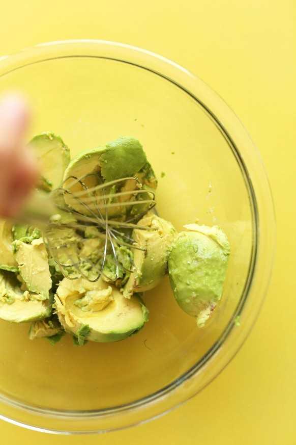 Romper aguacates para nuestra receta de tazón de arroz con coliflor y burrito