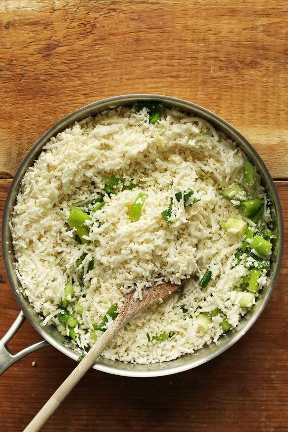 Mezclando arroz con coliflor y pimientos picantes para pimientos rellenos de arroz con coliflor mexicana