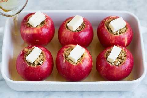 Manzanas en una fuente para hornear con azúcar morena y un poco de mantequilla en el centro. Se muestra antes de hornear.