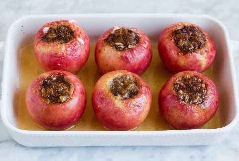 Las manzanas se muestran después de hornear en una fuente para hornear con jugo de manzana en el fondo.