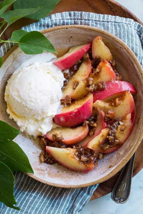 Manzana al horno cortada en rodajas con relleno de nuez sobre la parte superior y un lado de helado de vainilla.