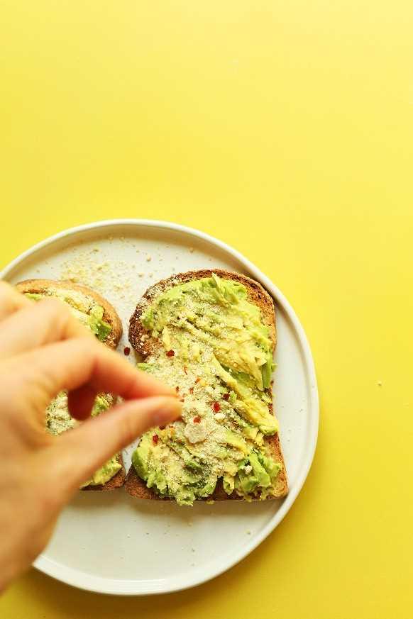 Espolvorea condimentos sobre una tostada de aguacate sin gluten para un desayuno vegano saludable