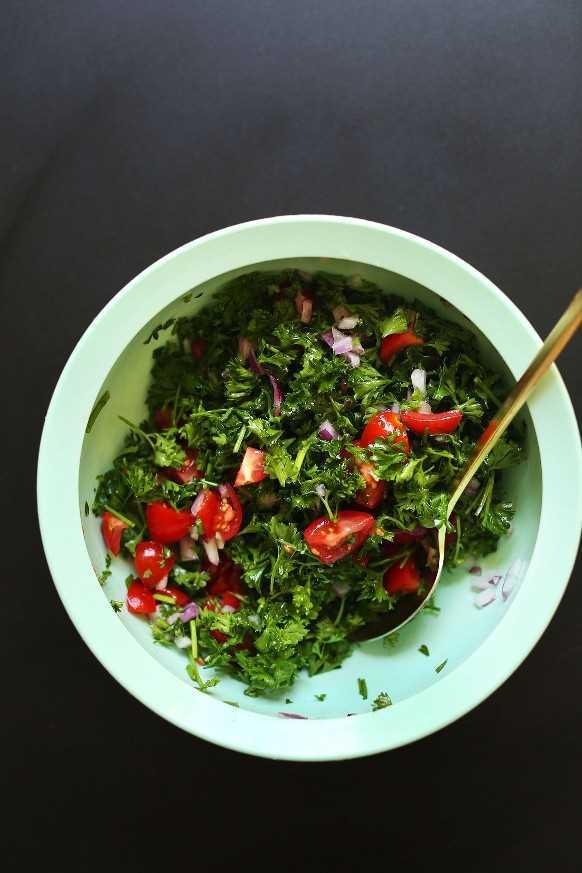 Mezclando ingredientes para una ensalada de perejil para cuencos mediterráneos veganos