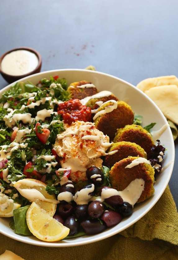 Salsa Tahini rociada sobre nuestra receta vegana del Tazón Mediterráneo