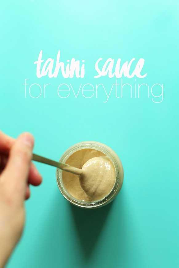 Agarrando una cucharada de salsa de tahini vegana sin gluten