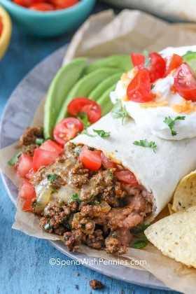 Feche acima de um burrito de carne moída em um prato, coberto com creme de leite, tomate picado e coentro.