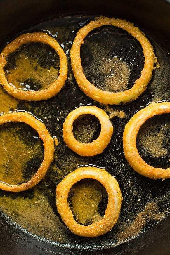 Aros de cebolla sin gluten que chisporrotean en una sartén de hierro fundido
