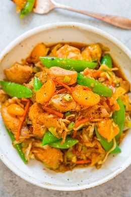 Salteado de pollo y mandarina con verduras en un tazón blanco