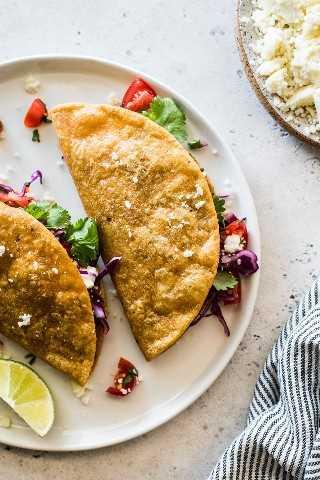 Tacos crujientes de papa en un plato blanco relleno de repollo rallado y pico de gallo.