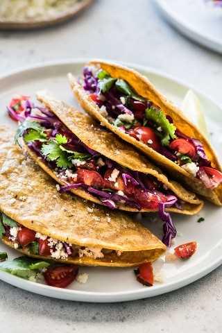 Tacos crujientes de papa rellenos de repollo rallado, pico de gallo y queso cotija.