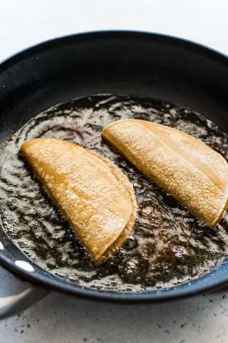 Tacos de papa fritos en una sartén grande.