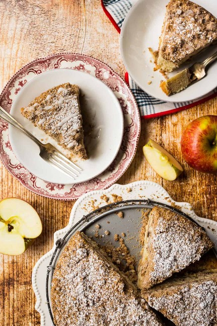 Rebanadas de pastel de café canela manzana en platos con manzanas frescas.