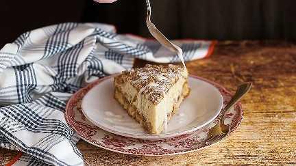 Rociando hielo sobre una rebanada de pastel de café de manzana fresca.